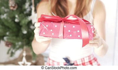 The girl holds out a beautifully packaged Christmas gift