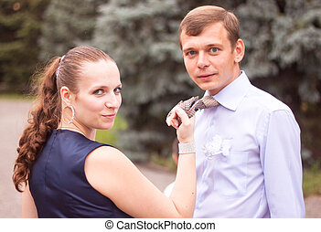 The girl holds the man for a tie
