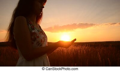 The girl holds the sun in hand