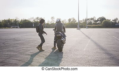 The girl in a leather jacket with a leather backpack on her shoulders, approaches the motorcycle where her boyfriend is waiting and they together to ride around the city on the motorcycle