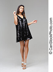 The girl in a little black sequins dress dancing