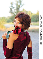 The girl in a red dress with a rose
