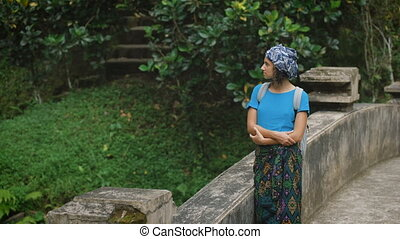 The girl in a skullcap, a blue jacket and a cape on a waist travels around the island of Bali. She costs on a terrace at the temple. Looks in a distance and poses for the photographer.