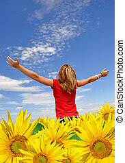 The girl in a sunflower field looks at horizon