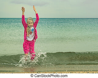 The girl in a warm suit plays in the cold sea.