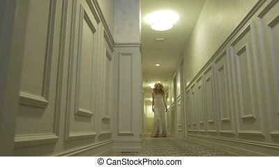 The girl in a wedding dress posing in the corridor