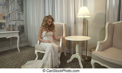 The girl in a wedding dress sitting in a chair