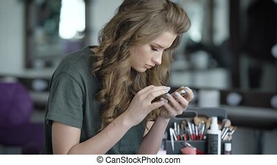 The girl in beauty shop. The blonde sits on a chair and looks through news on the phone. The woman is made already up and laid. Against the background of a brush for a make-up.