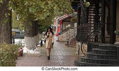 The girl in beige coat walks around and read message