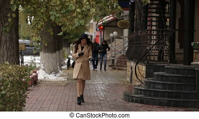 The girl in beige coat walks around and uses a smartphone