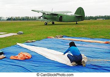 The girl in dark blue straightens a parachute
