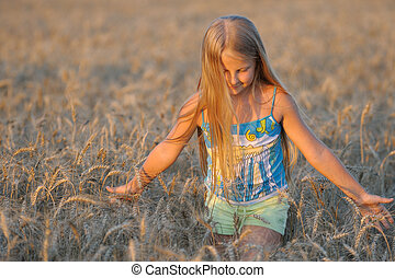 The girl in filed wheats. Warm light sunset