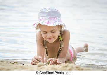 The girl in panama lying on the sand by the river