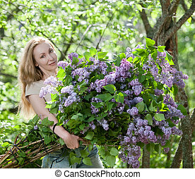 The girl in park with a huge bouquet of a lilac