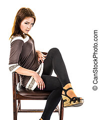 the girl in sandals is sitting on an old wooden armchair
