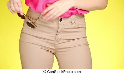 The girl in stylish narrow beige jeans and fashion...