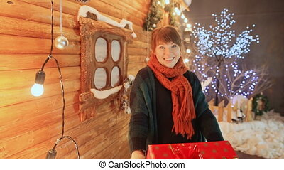 The girl in the background of a wooden fairy-tale house funny and jokingly gives a gift to the viewer. Christmas and New Year theme.