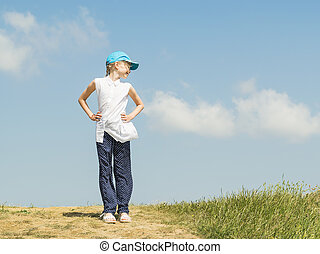 The girl in the blue baseball cap is standing on top of the hill turning his head.