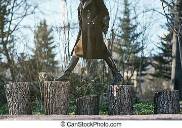 The girl in the forest steps over from the stump to the stump. Choose a difficult way to travel