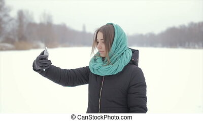 The girl in the green scarf and a black jacket makes selfie