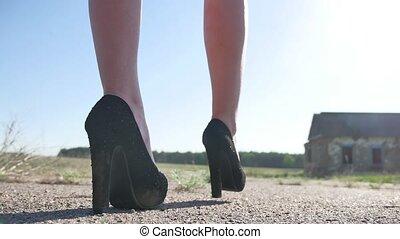 The girl in the heels is walking along the street. Feet...