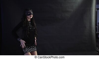 The girl in the mask dances on a black background