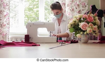The girl in the medical mask, protection from coronavirus. Atelier in quarantine and state of emergency. Small business after the virus. The master sews the fabric on the sewing machine