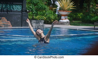 The girl in the pool. The brunette in a black bathing suit in the pool. Woman dancing in the pool. Young in a good mood, smiling and laughing. A trip to Bali is very good.