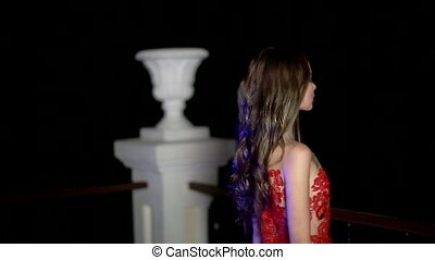 The girl in the red dress stands on the balcony