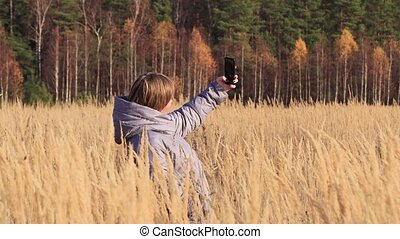 The girl in the tall grass, she uses the Internet on her phone and talks