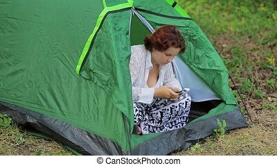 The girl in the tent with the phone - A girl sits in a green...