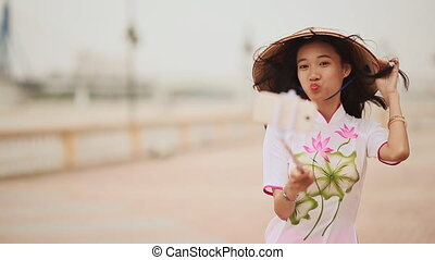 The girl in the Vietnamese national traditional costume photographs herself using the phone.