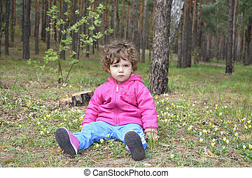The girl in the woods sitting on a stump.
