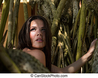 The girl in tropics, the beautiful young girl walking among palm trees