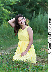 The girl in yellow dress sitting on grass