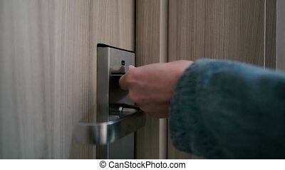 The girl inserts a key card into the door of the hotel room and goes inside
