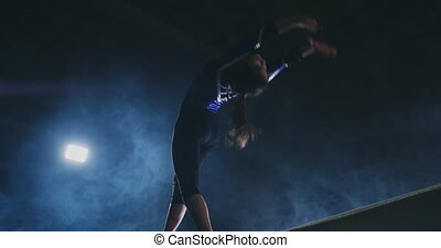 The girl is a professional athlete performs gymnastic...