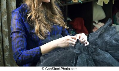The girl is a seamstress working in a sewing workshop....