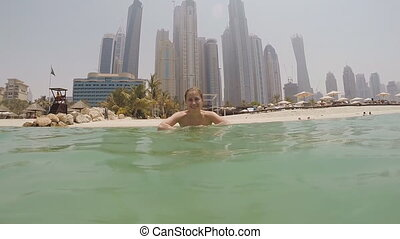 The girl is bathed in the sea and sprinkles water on against the background of skyscrapers Dubai. Slow motion shooting.