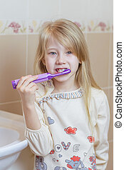 The girl is brushing her teeth with an electric brush in the bathroom.