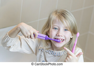 The girl is brushing her teeth with two different toothbrushes.