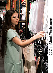 The girl is choosing a dress in the store