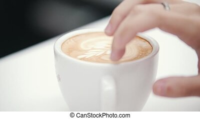 The girl is driving her fingers over a cup of coffee