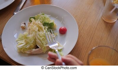 the girl is eating a salad in the first person cafe. slow...