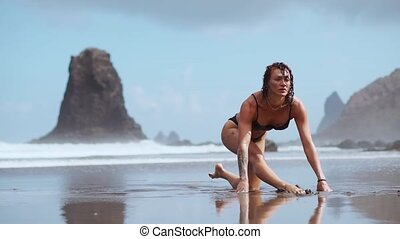 The girl is engaged in stretching and gymnastics on the shore of the ocean.