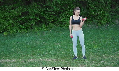 The girl is exercising with a dumbbell - Girl trains using a...