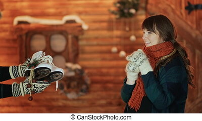 The girl is given white skates, which she is very happy about against the background of a magical fairy-tale house. Christmas and New Year theme.