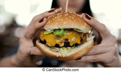 The girl is holding a big and tasty cheeseburger.