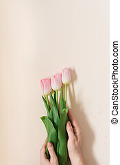 The girl is holding a bouquet of delicate pink tulips on a white background. Copy space. Mother's day. The concept of a floral blog