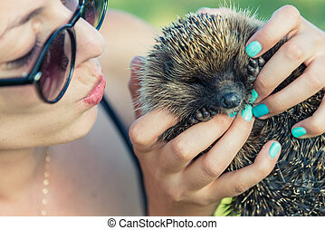 The girl is holding a hedgehog